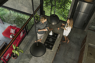 Top view of couple standing in modern design kitchen with glass facade surrounded by lush garden - SBOF00832