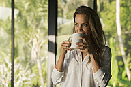 Smiling woman drinking coffee at home in front of lush tropical garden - SBOF00835