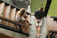 Top view of couple having a talk on stairs in modern design house - SBOF00838