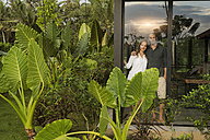 Garden view of smiling couple looking outside of their design house surrounded by lush tropical garden - SBOF00841