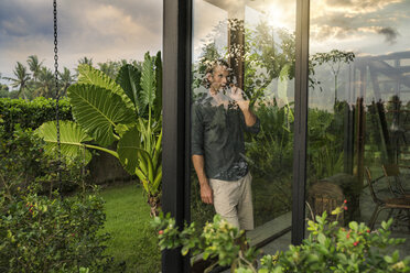 handsome man standing behind glass facade of design house talking on smartphone surrounded by lush tropical garden - SBOF00844