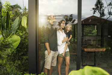 Garden view of parents with their young son looking outside of their design house surrounded by lush tropical garden - SBOF00847
