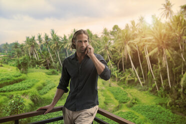 Handsome man leaning on balkony speaking on smartphone with stunning view of tropical landscape - SBOF00850