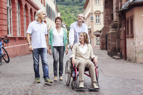 Germany, Heidelberg, senior friends with woman in wheelchair on city trip - PNPF00003