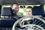 Smiling couple in car with wheelchair in boot - PNPF00012