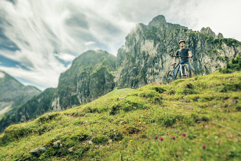 Germany, Bavaria, Pfronten, young man with mountain bike on alpine meadow near Aggenstein - PNPF00021