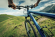 Germany, Bavaria, Pfronten, mountainbiker riding downhill on alpine meadow near Aggenstein - PNPF00024