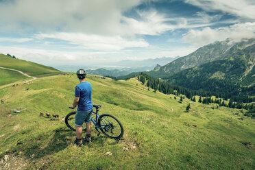 Germany, Bavaria, Pfronten, man with mountain bike on alpine meadow near Aggenstein - PNPF00027