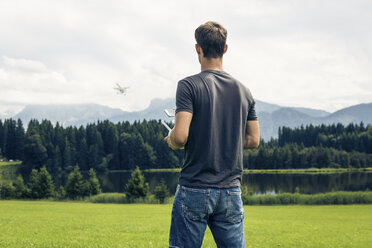 Germany, Bavaria, Pfronten, young man flying his drone at lakeside - PNPF00033