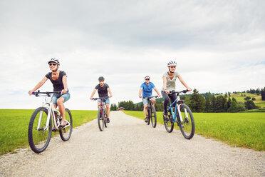 Germany, Bavaria, Pfronten, family riding mountain bikes in the countryside - PNPF00036