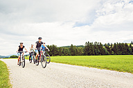 Germany, Bavaria, Pfronten, family riding mountain bikes in the countryside - PNPF00039