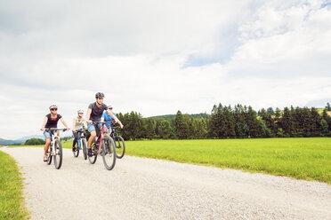 Germany, Bavaria, Pfronten, family riding mountain bikes in the countryside - PNPF00039