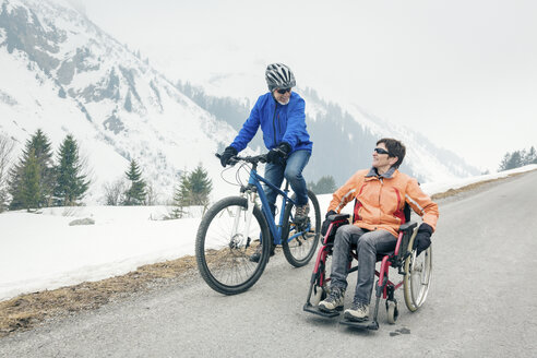Austria, Damuels, senior couple with bike and wheelchair enjoying a winter day - PNPF00042