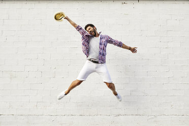 Happy man jumping mid-air in front of white wall - JRFF01446