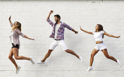 Three friends jumping mid-air in front of white wall - JRFF01449