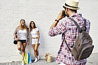 Man taking picture of two young women standing at white wall with bags - JRFF01452