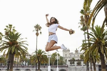 Spain, Barcelona, happy woman jumping mid-air surrounded by palm trees - JRFF01464