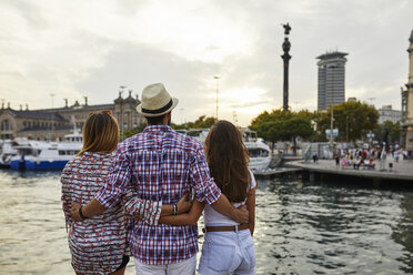 Spain, Barcelona, three tourists embracing at the waterfront in the city - JRFF01470