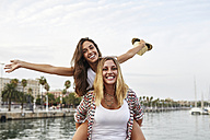 Spain, Barcelona, young woman giving her friend a piggyback ride - JRFF01473