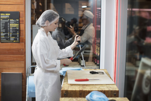 Woman in a butchery sharpening knife - ZEF14635