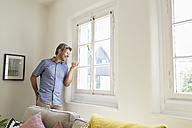 Mature man at home standing by window, using smartphone - PDF01278
