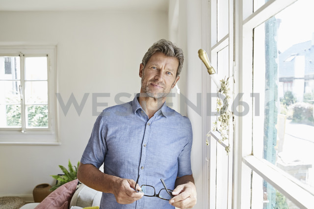Mature man at home eaning at window, holding glasses - PDF01296
