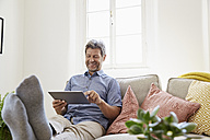 Man sitting on couch at home, using digital tablet - PDF01299