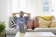 Man sitting on couch at home, relaxing - PDF01308