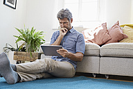 Man sitting in living room, using digital tablet - PDF01311