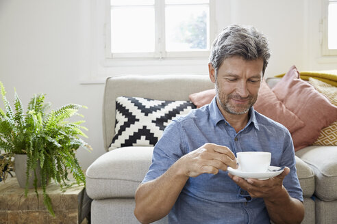Mature man at home sitting in front of couch, drinking coffee - PDF01317