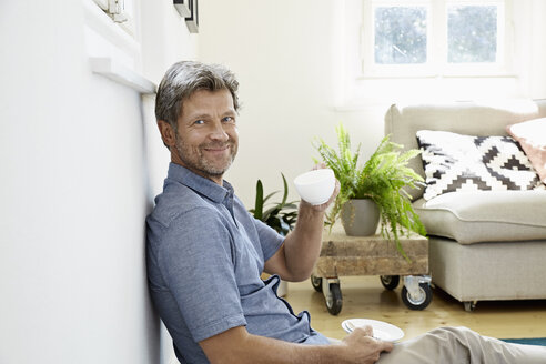 Mature man at home sitting in front of couch, drinking coffee - PDF01323
