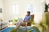 Man working at home using laptop - PDF01326