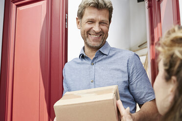 Mature man receiving a package at his door - PDF01332