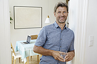 Mature man leaning against door case holding glass of water - PDF01338
