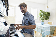 Mature man playing piano at home - PDF01341
