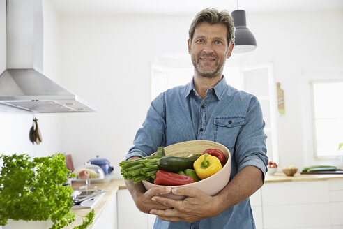 Mature man standing in kitchen, holding a bowl with vegetables - PDF01353