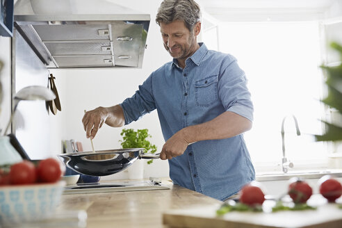 Mature man in his kitchen frying vegetables - PDF01356