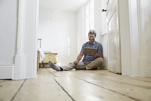 Marture man sitting on floor of his bedrom, using digital tablet - PDF01374