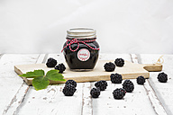 Glass of homemade blackberry jam, blackberries and leaf on wooden board - LVF06288