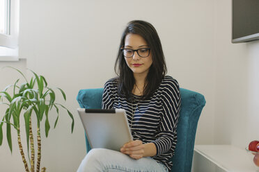 Portrait of young woman using tablet at home - MOMF00248