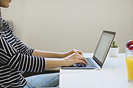Young woman using laptop at home, partial view - MOMF00251