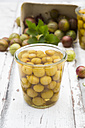 Jar of preserved gooseberries and gooseberries on wood - LVF06294
