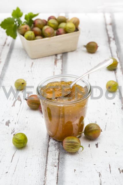 Jar of gooseberry jam and gooseberries on wood - LVF06297