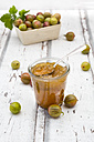 Jar of gooseberry jam and gooseberries on wood - LVF06297