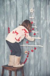 Little girl decorating the wall at Christmas time - RTBF01027
