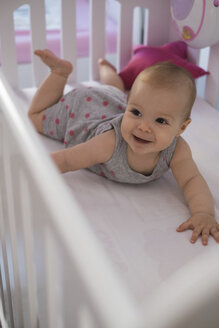 Happy baby girl lying in crib - MOMF00261