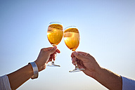 Couple clinking spritz glasses before blue sky - DIKF00279