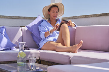 Woman with tablet relaxing on sun deck - DIKF00285