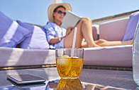 Glass of Crodino, smartphone and woman relaxing on sun deck in background - DIKF00288