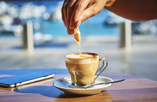 Close-up of woman's hand pouring sugar into glass of Espresso Macchiato - DIKF00291